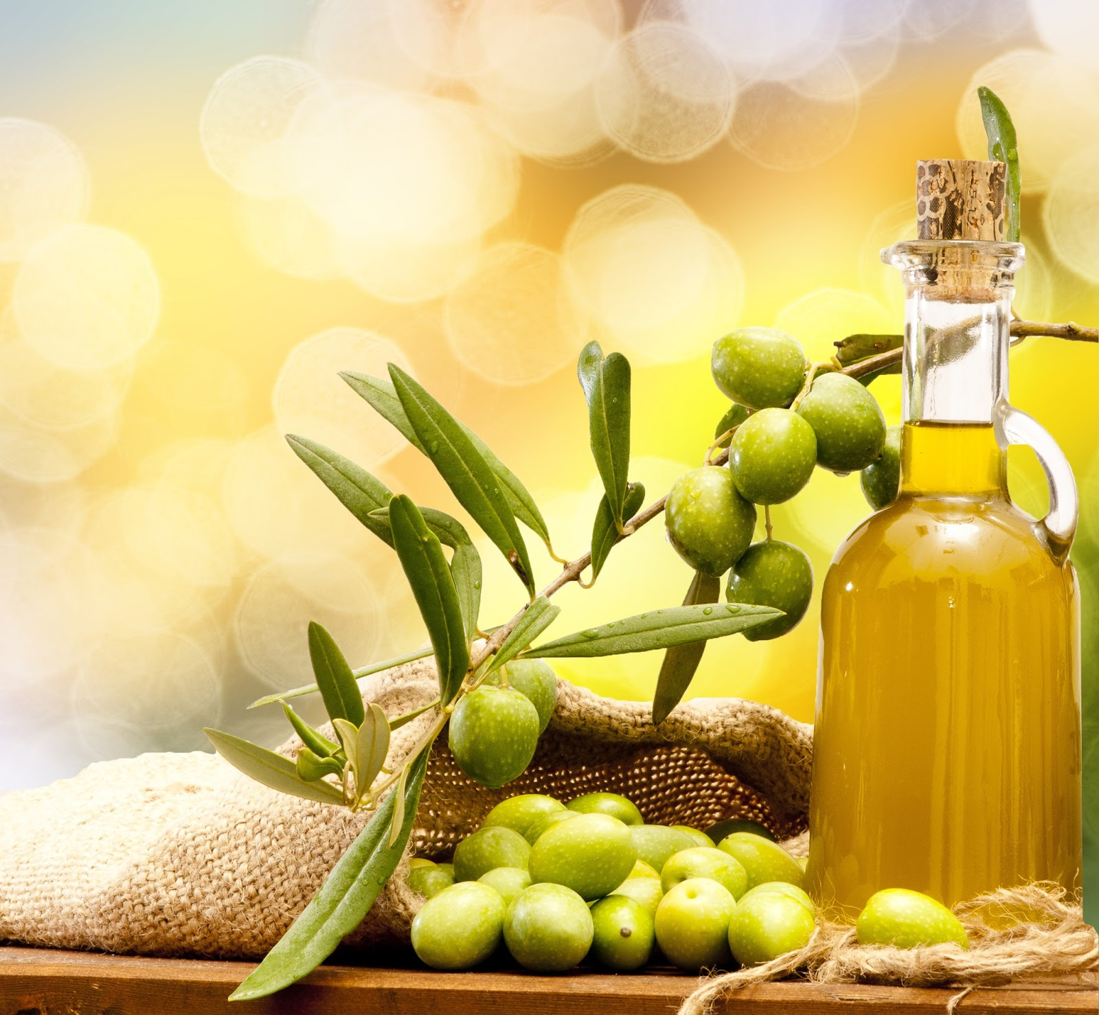 Green olives with a bottle of olive oil on a yellow background
