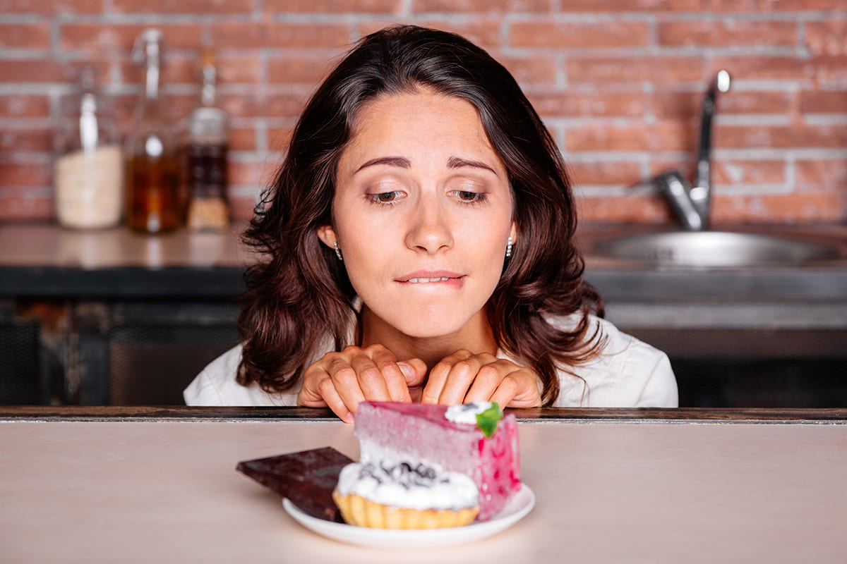 Woman looking at a plate of sweets with longing and desire