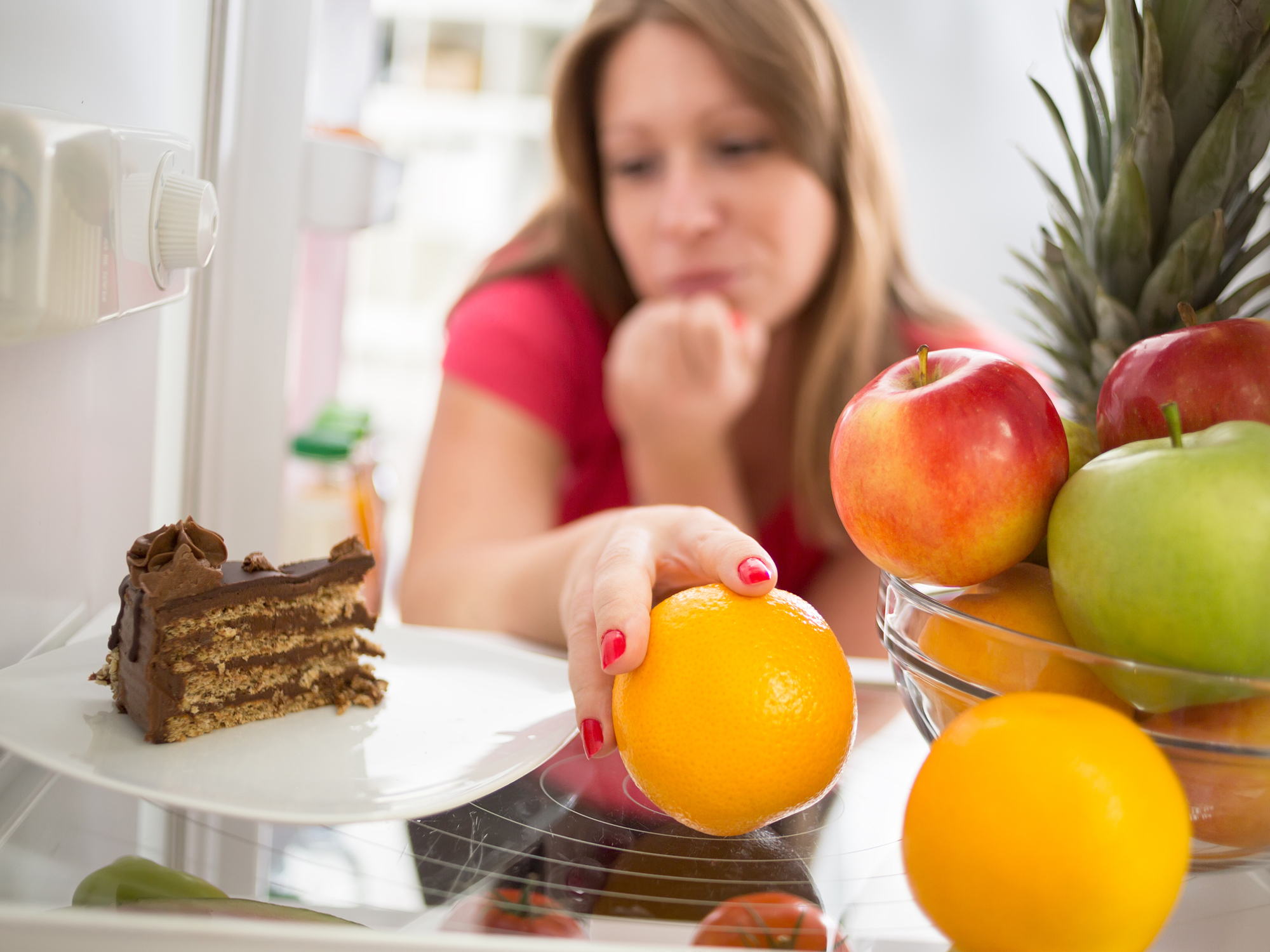 Woman looking at a piece of cake while reaching to grab a fruit instead