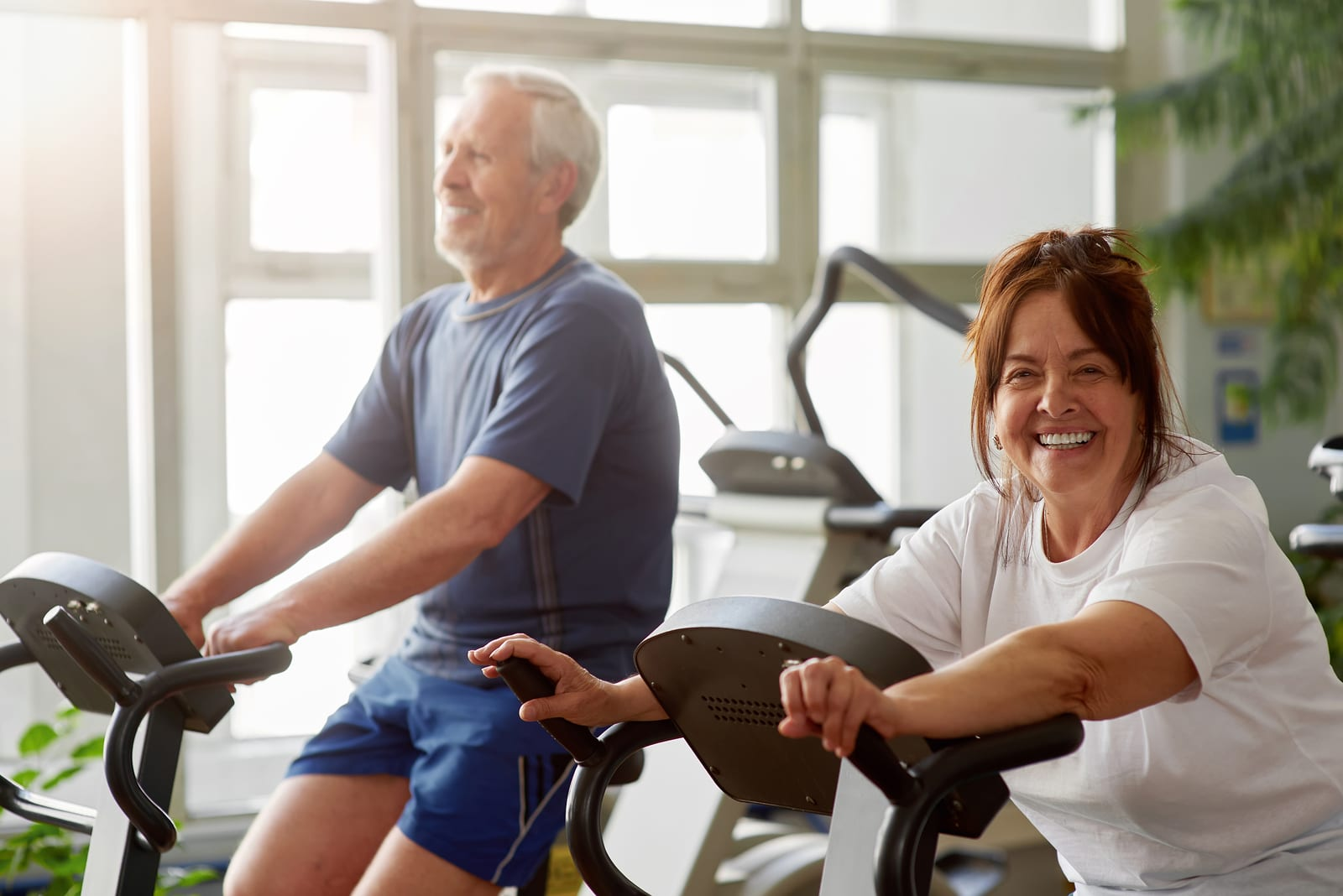 Man and woman in their 50s on stationary bikes
