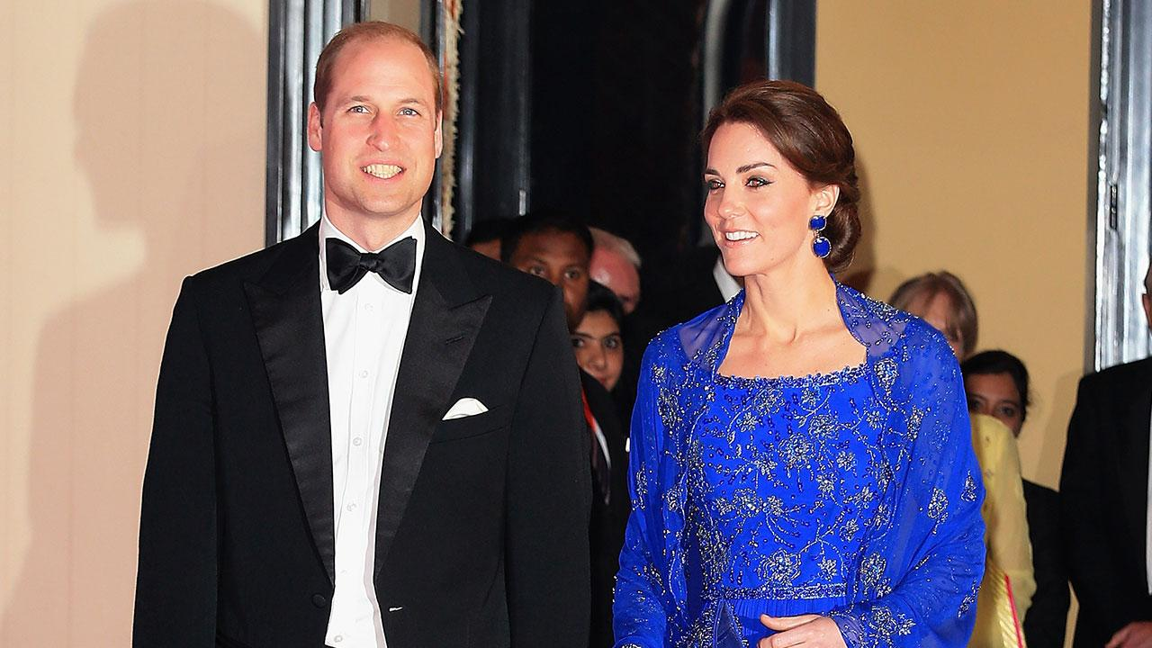 Prince William and Kate Middleton during an event, Kate is wearing a royal blue dress with a matching beaded shawl