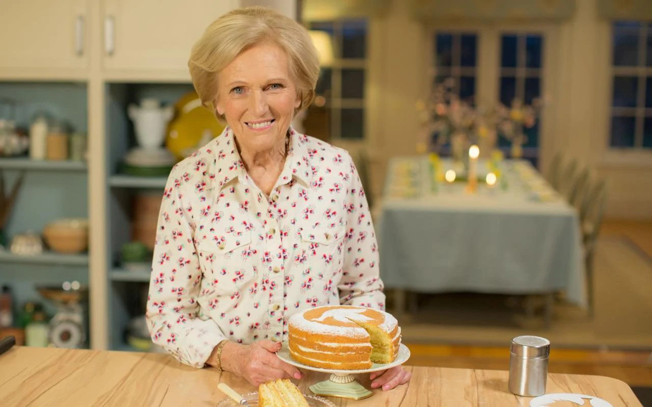 Mary Berry standing behind a countertop arranged with a freshly made cake