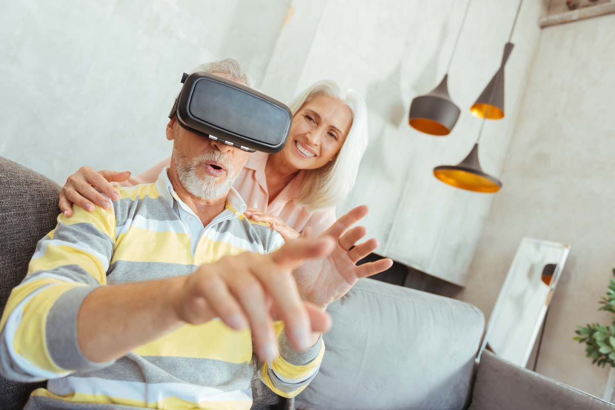 An elderly couple with the man wearing VR glasses