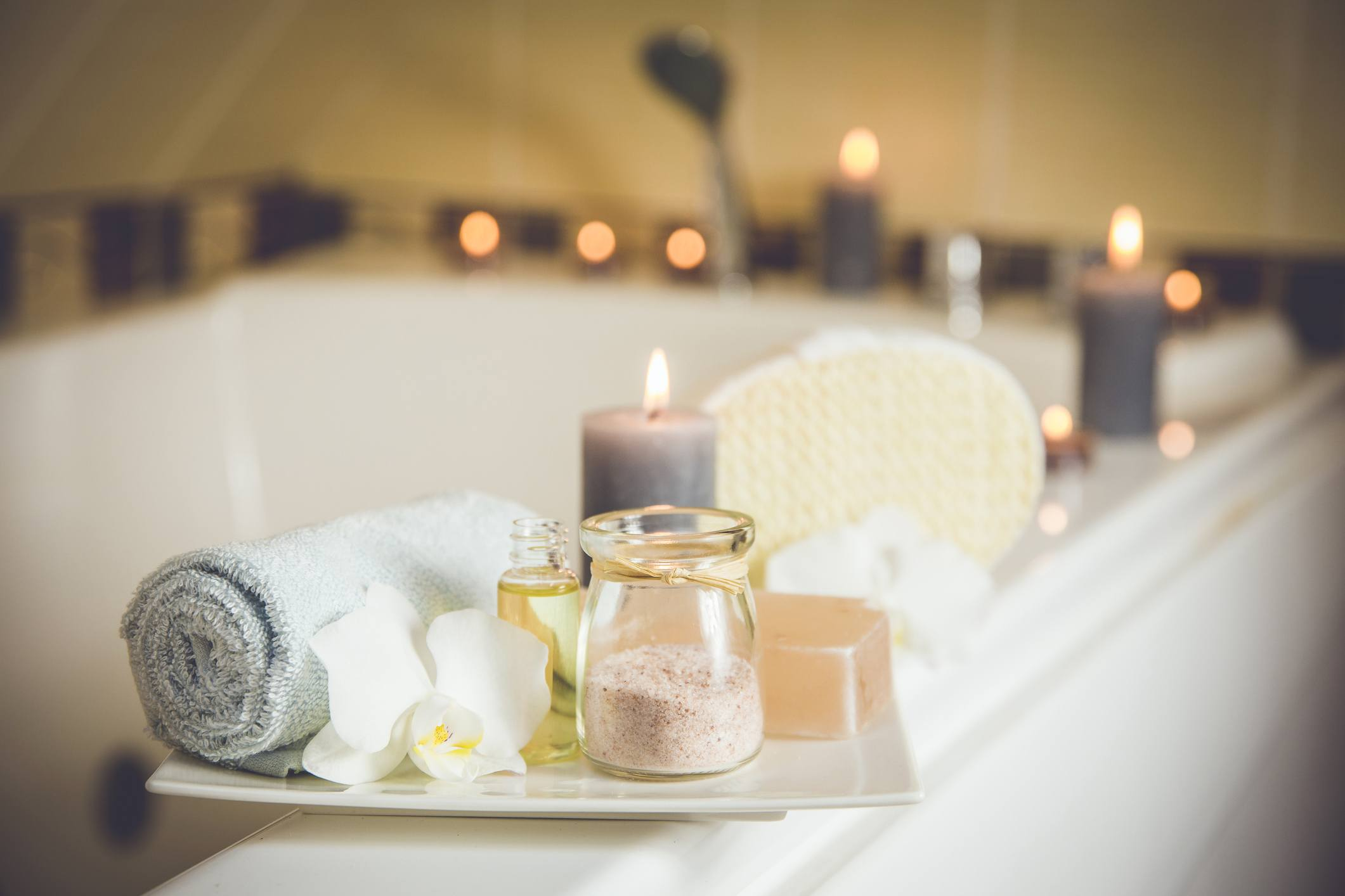 bathtub arrangement with scented candles, towels, and decorations