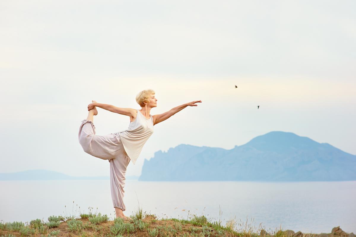 Older woman doing yoga outside