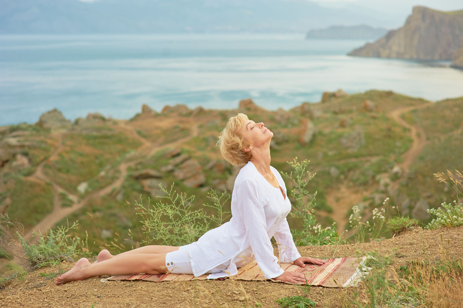 Older woman doing yoga in the open