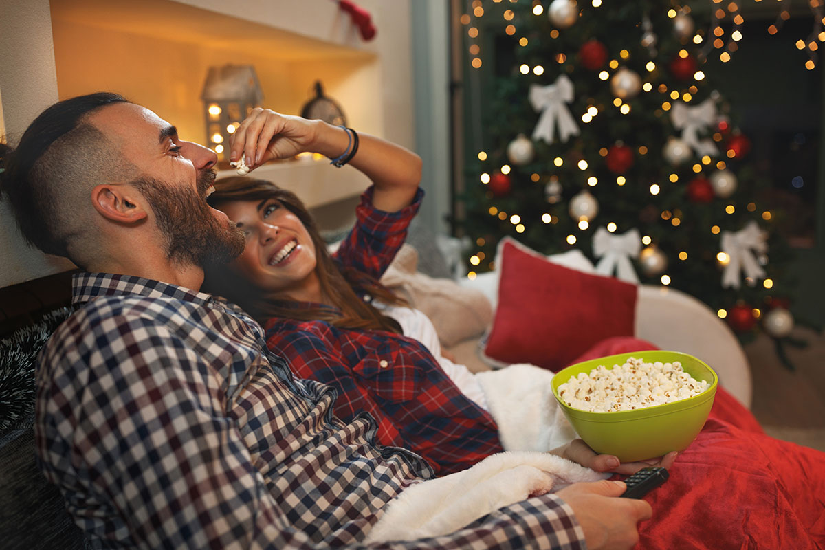 Couple at Christmas enjoy with popcorn while watching tv