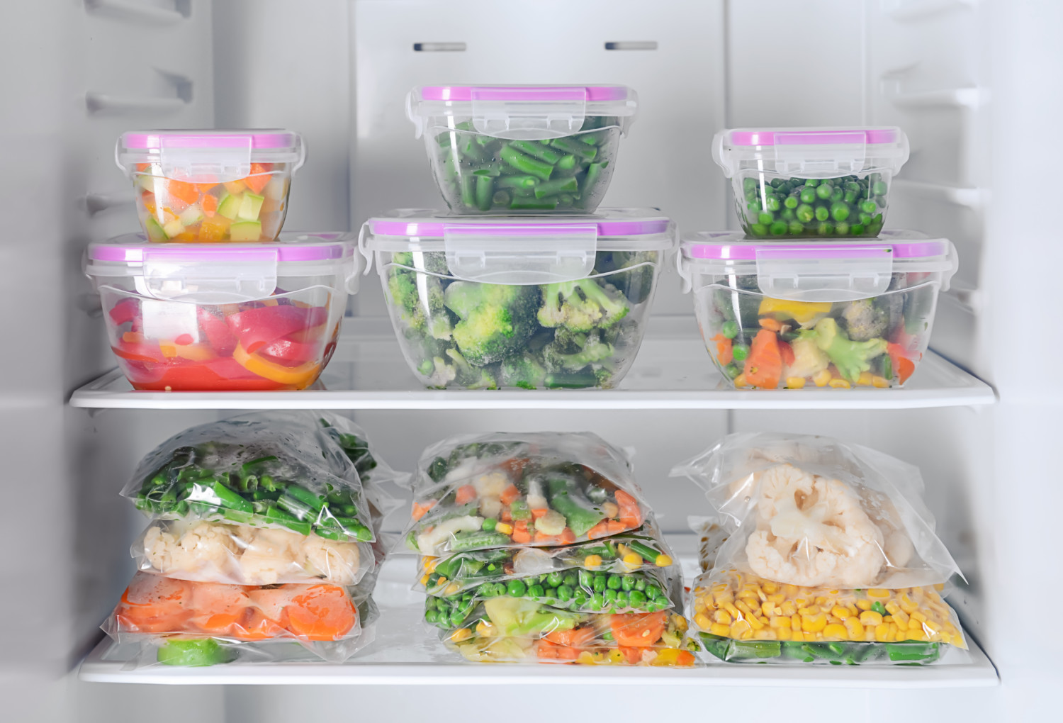 Containers and plastic bags with vegetables in fridge