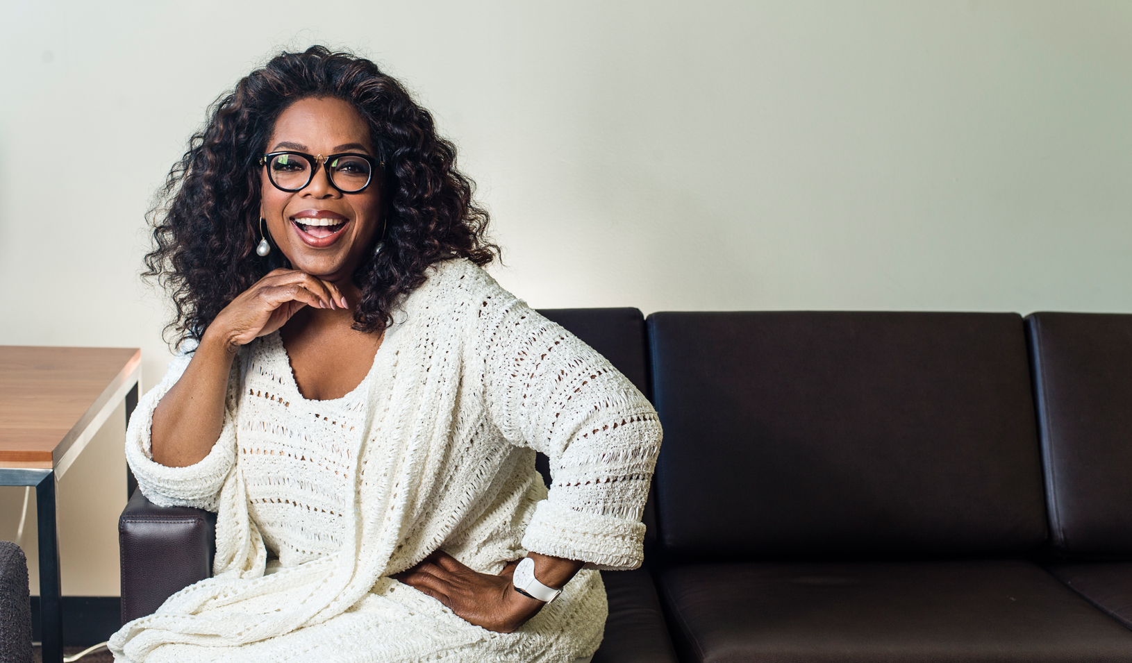 Oprah sitting on a couch smiling at the camera