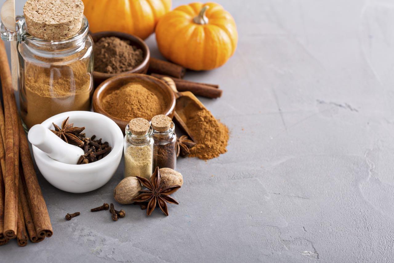 Pumpkin pie spice in a glass jar with ingredients
