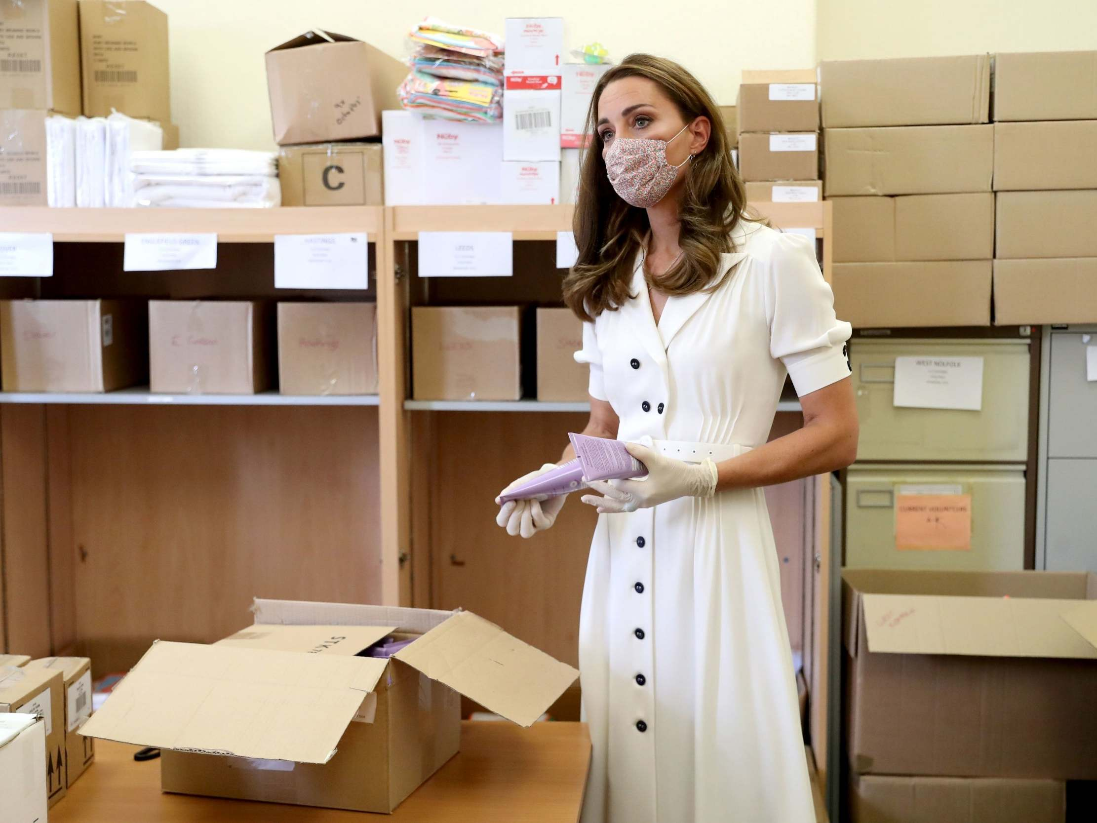 The Duchess of Cambridge, wearing a face mask, helps to unpack supplies during a visit to Baby Basic UK & Baby